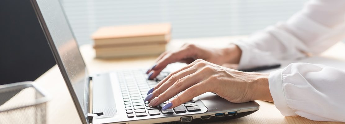 Business, technology and people concept - close up of woman's hands typing in laptop