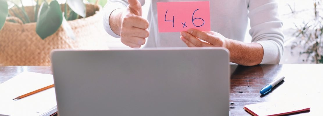 teacher showing multiplication flash card and thumbs up to student on computer during online lesson
