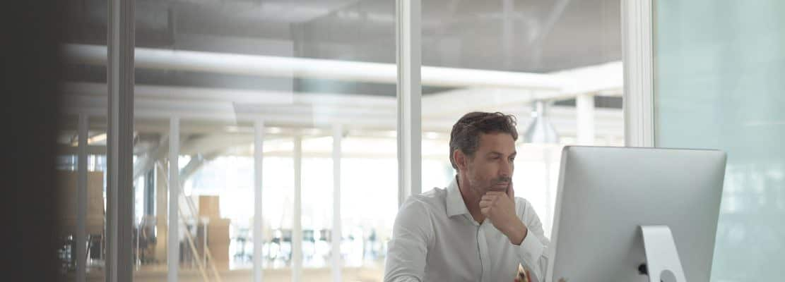Thoughtful Caucasian business male executive working on computer at desk