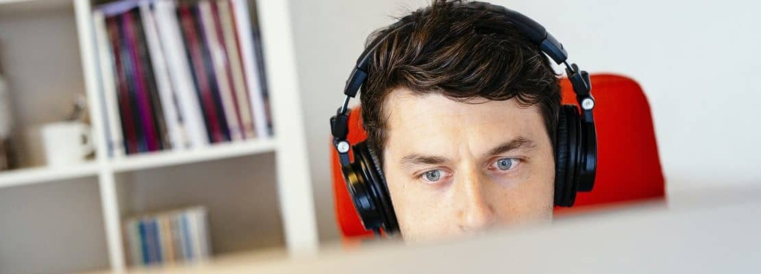 Businessman wearing headphones while using computer in office