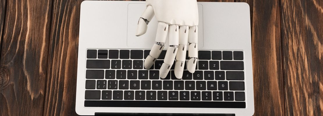 cropped shot of robot working with laptop on wooden surface