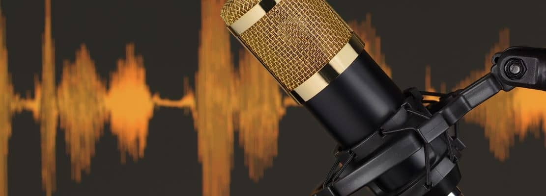 Gold colored condenser microphone over waveform.