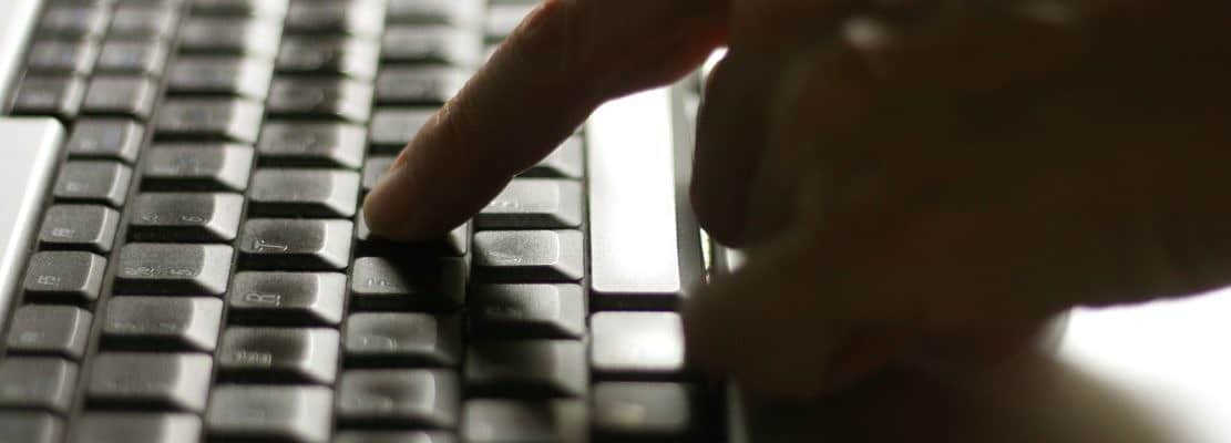 Using laptop, hands typing on the laptop keyboard