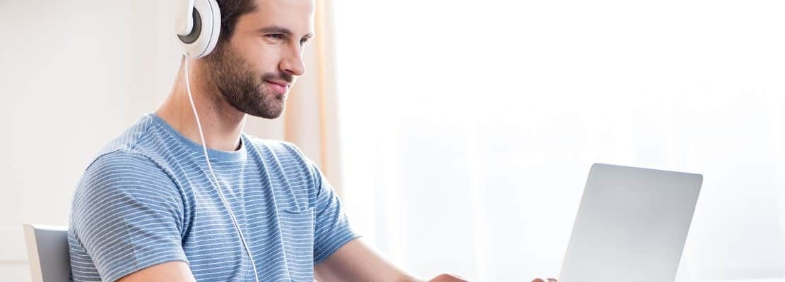 Young smiling man in white headphones using laptop