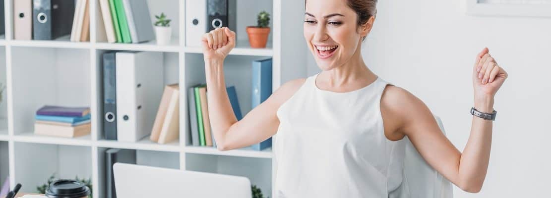 successful businesswoman celebrating at workplace and looking at laptop