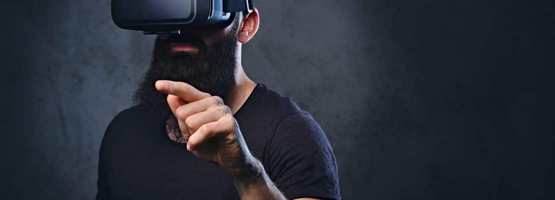A man with tattoos on arms wearing VR glasses.