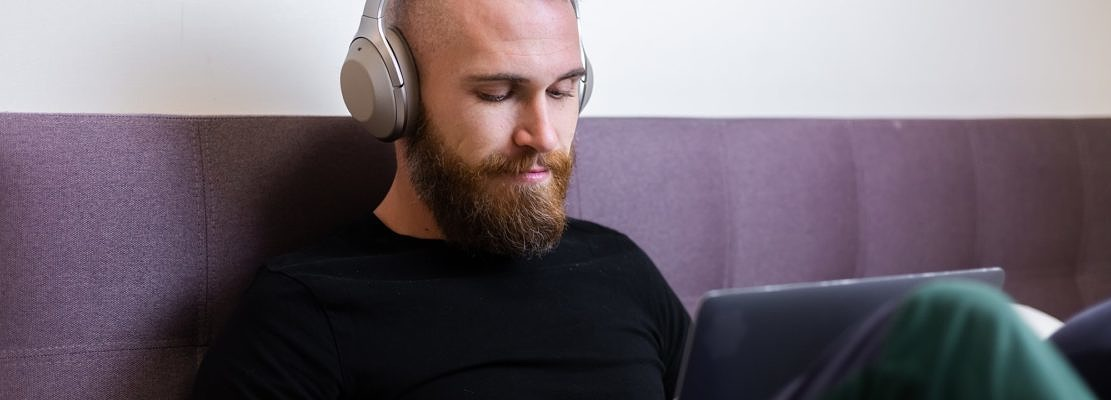 Caucasian bearded man in headphones in bedroom on bed working on laptop from home, typing, thinking.