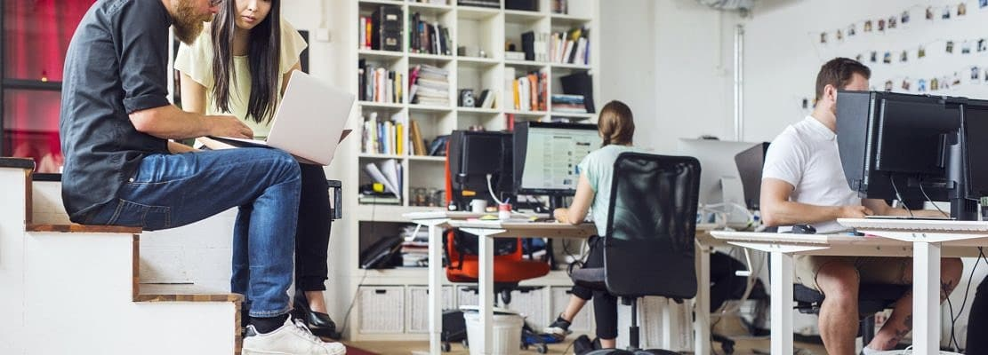 Coworkers using computers at office