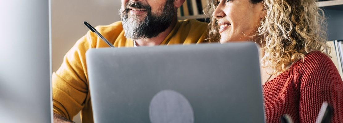 People at work at home with internet connection and computer laptop in couple - man and woman