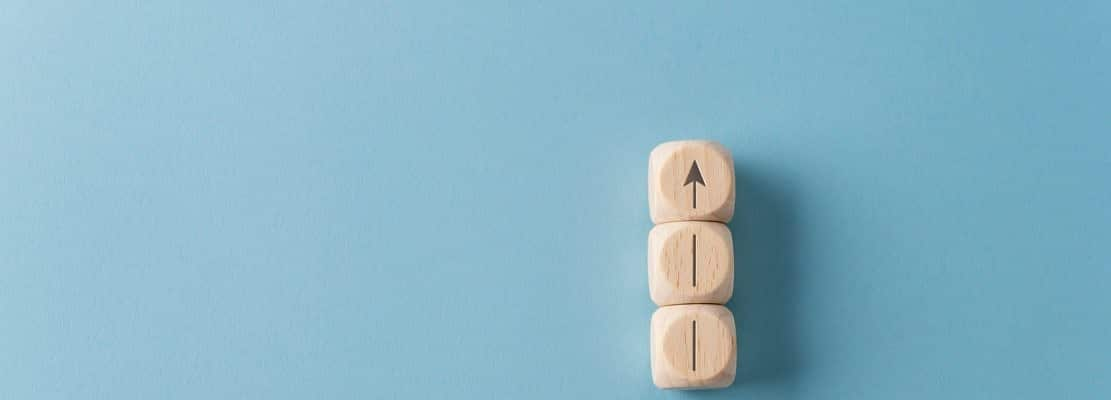 Wooden dices with arrow pointing upwards