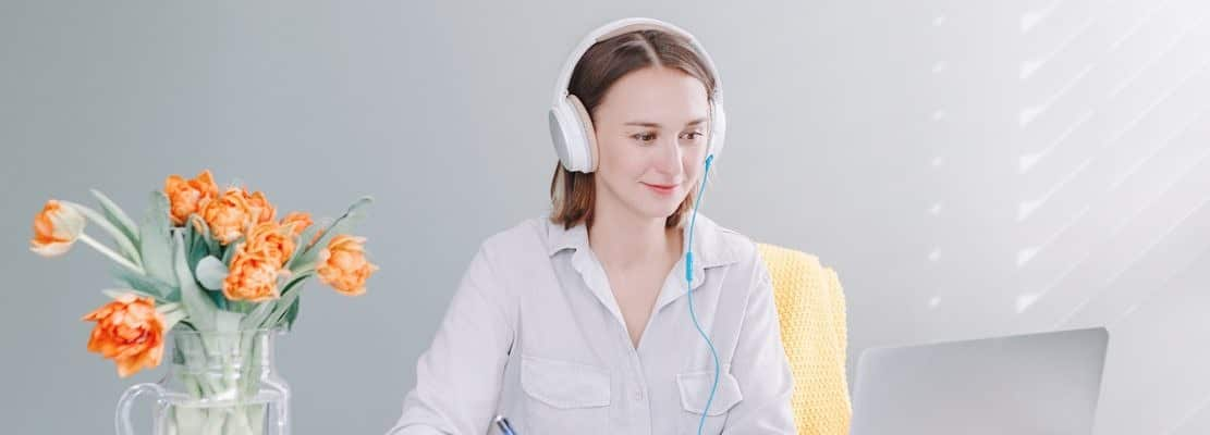 Busy Caucasian business woman in headphones working studying on laptop from home office.