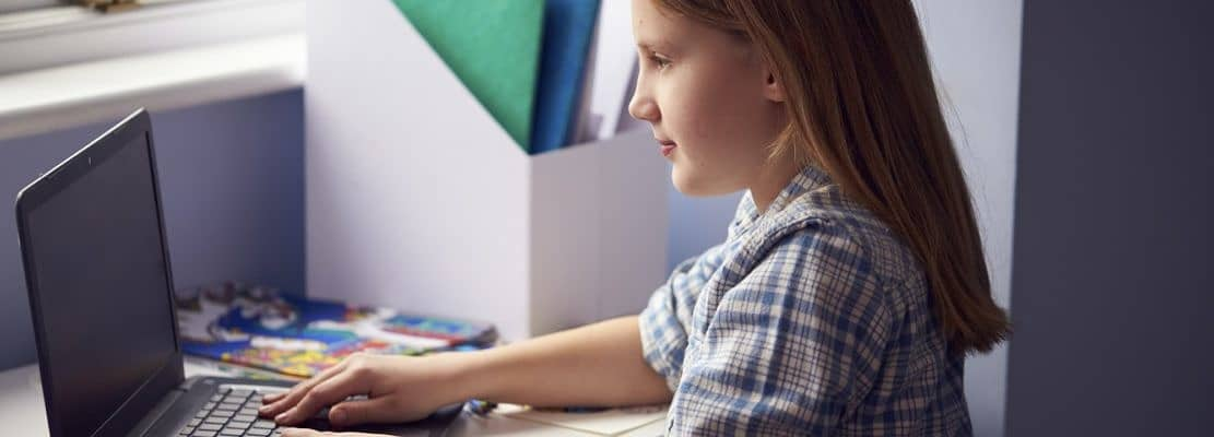 Girl Sitting At Desk Home-Schooling Using Laptop For Online Learning During Health Pandemic