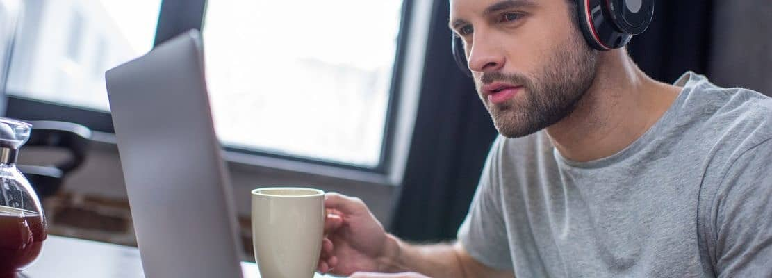 Young concentrated man in headphones using laptop and drinking coffee