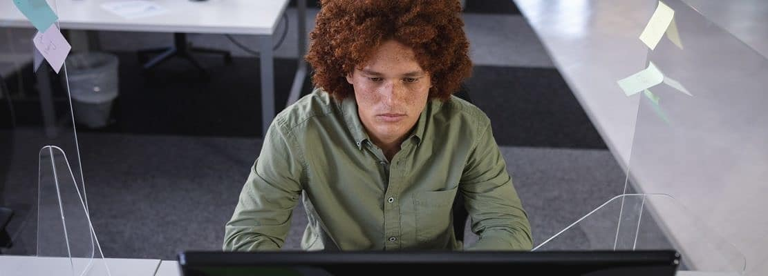 Mixed race businessman sitting in office in front of computer near sneeze shield