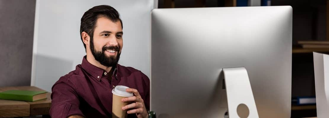 smiling businessman working at computer in office