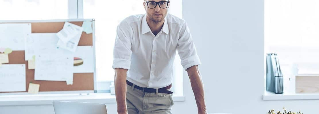 Real manager. Handsome young man in glasses looking at camera while leaning to the table in office
